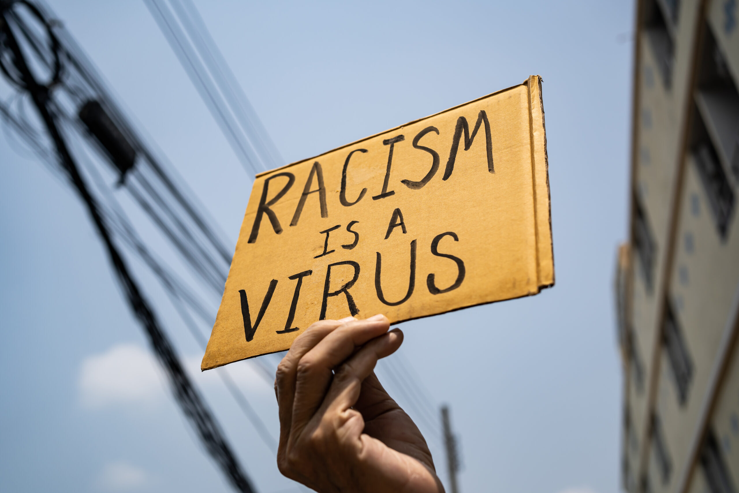 A man holding Racism is a Virus sign